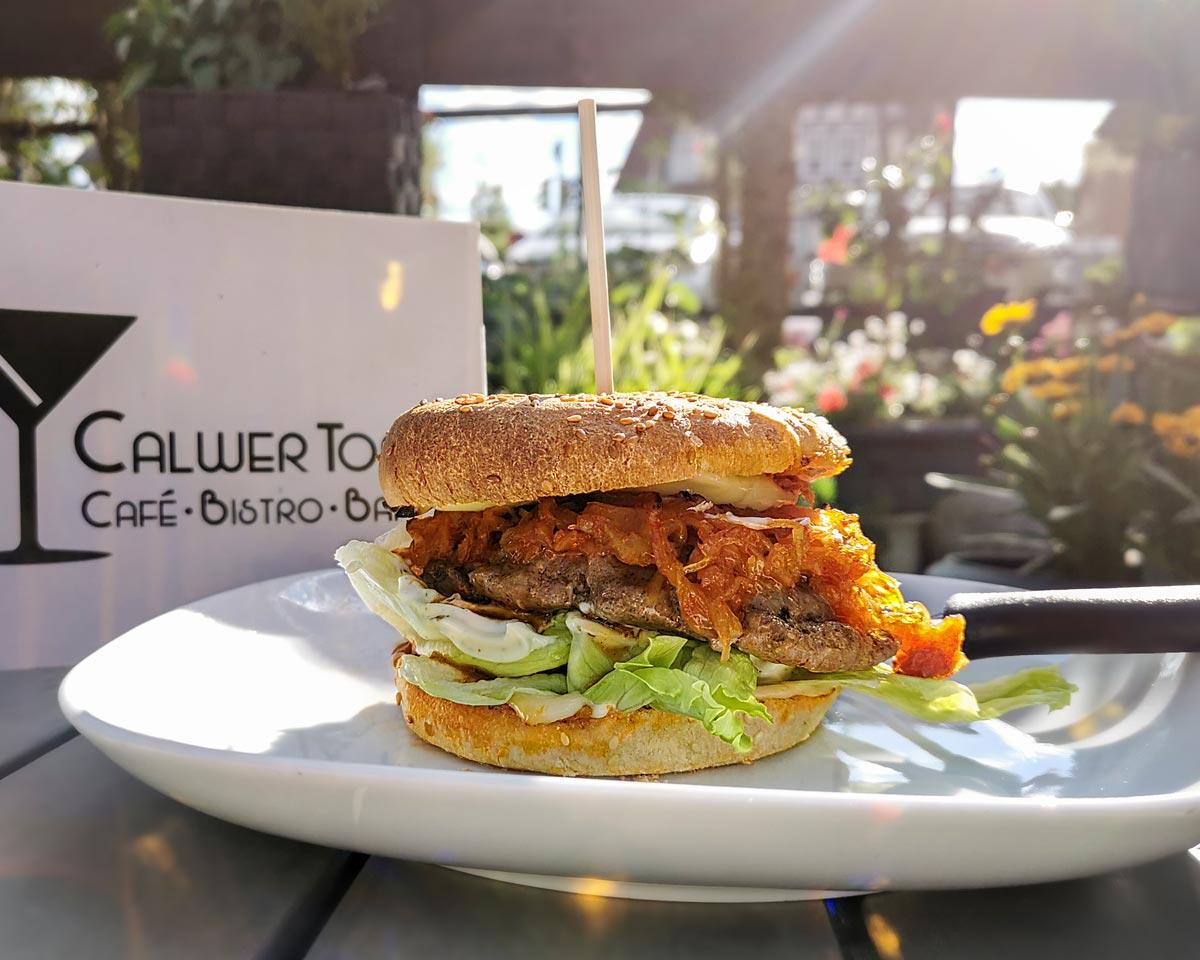 Burger mit Fleisch, Kraut und Salat auf einem weißen Teller. Speisekarte vom Calwer Tor sowie Blumen im Hintergrund.