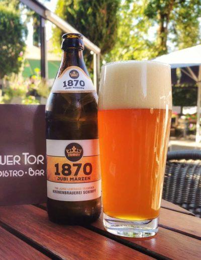 Bierflasche und Bierglas auf einem Holztisch im Biergarten des Calwer Tor in Weil der Stadt